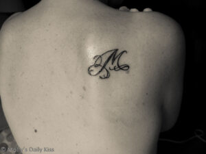 Letter M tattoo on back