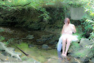 Naked woman bathing in the stream