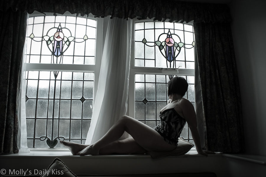 sexy woman sitting in a window seat