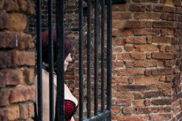 Sexy woman locked to castle gates