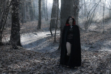 Cloaked woman naked in the woods