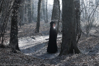 cloaked woman in the woods
