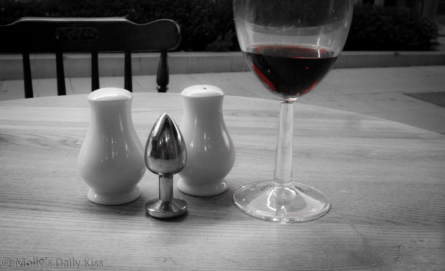 Metal butt plug on restaurant table with wine