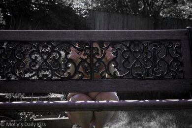 Peeking out naked from behind a garden bench
