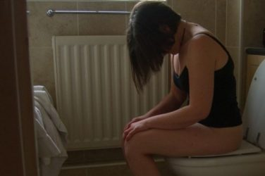 Woman sitting on the toilet having a pee