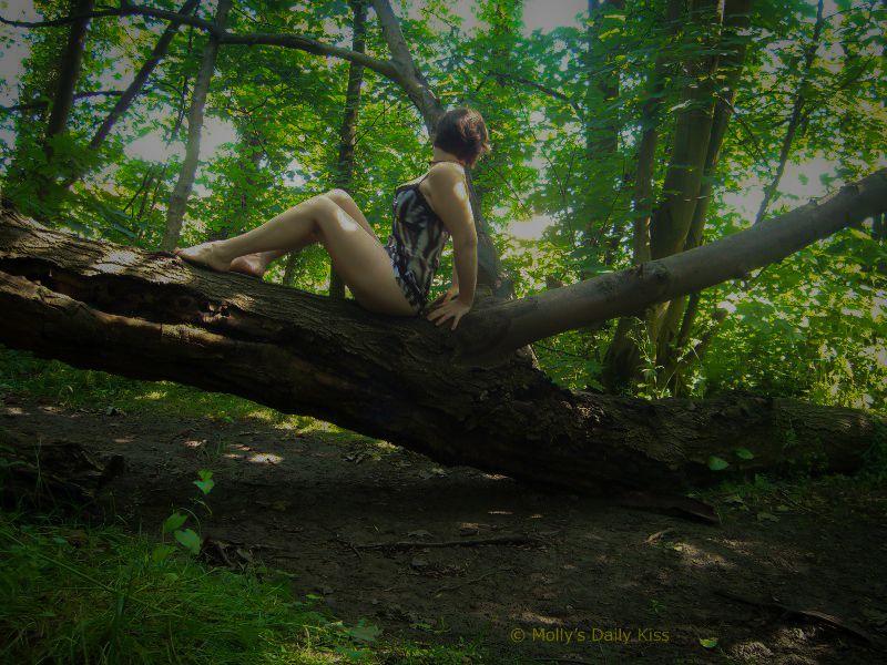 Woman sitting on a tree in underwear