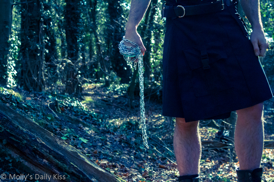 Man in wood wearing hunters kilt with chain wrapped round his fist