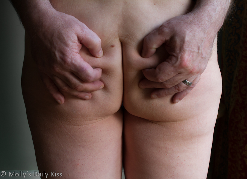 Male hands pinching mollys bare bottom