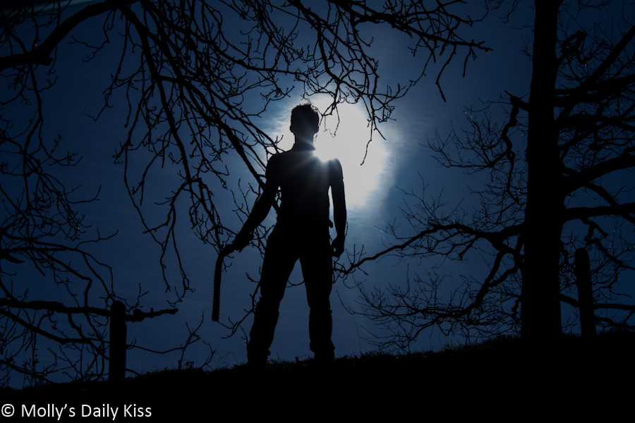 Dark silhouette image if man holding belt