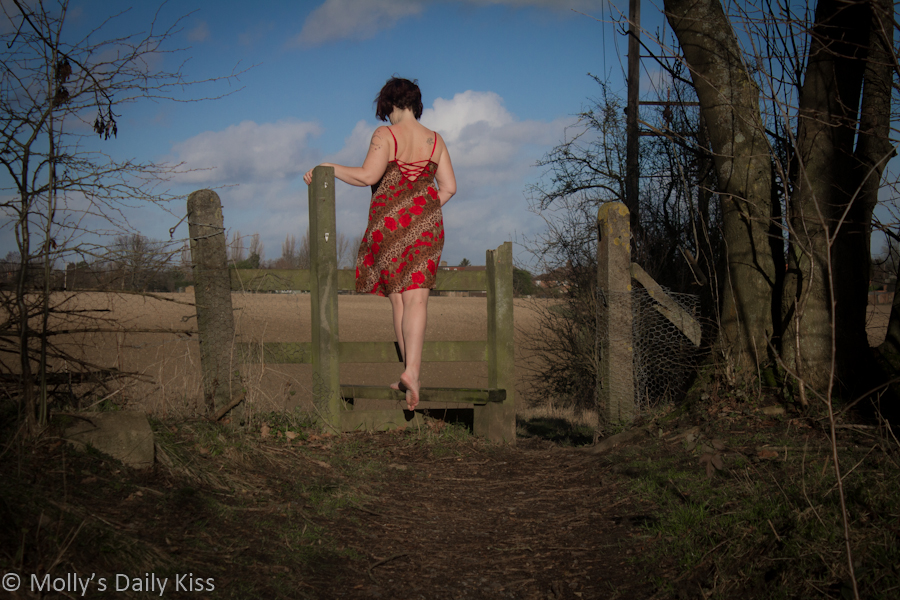 Woman in lingerie climbing over stile