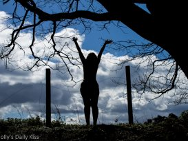 Naked women reaching up to the sun silhouette