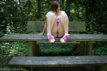 Sitting on picnic table showing a flash of pussy between legs