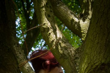 Molly climbing in tree wearing braces and topless