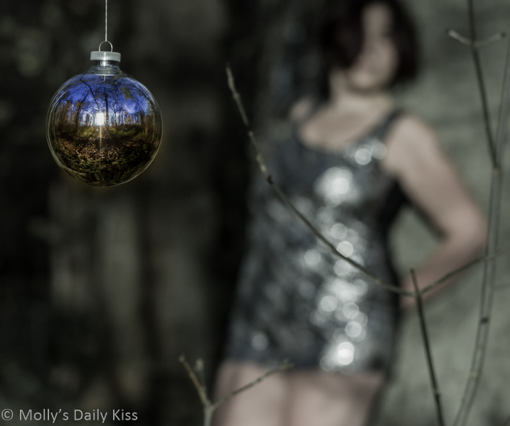 Colour Christmas bauble with sexy woman behind it