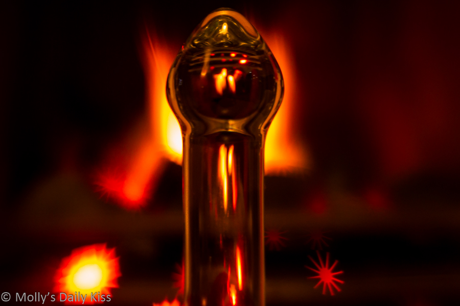 Glass dildo in front of fireplace
