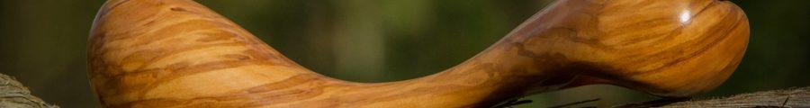 Wooden dildo in sunlight in the woods