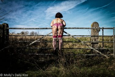 Leaning over gate in pink panties and socks, farmer girl,
