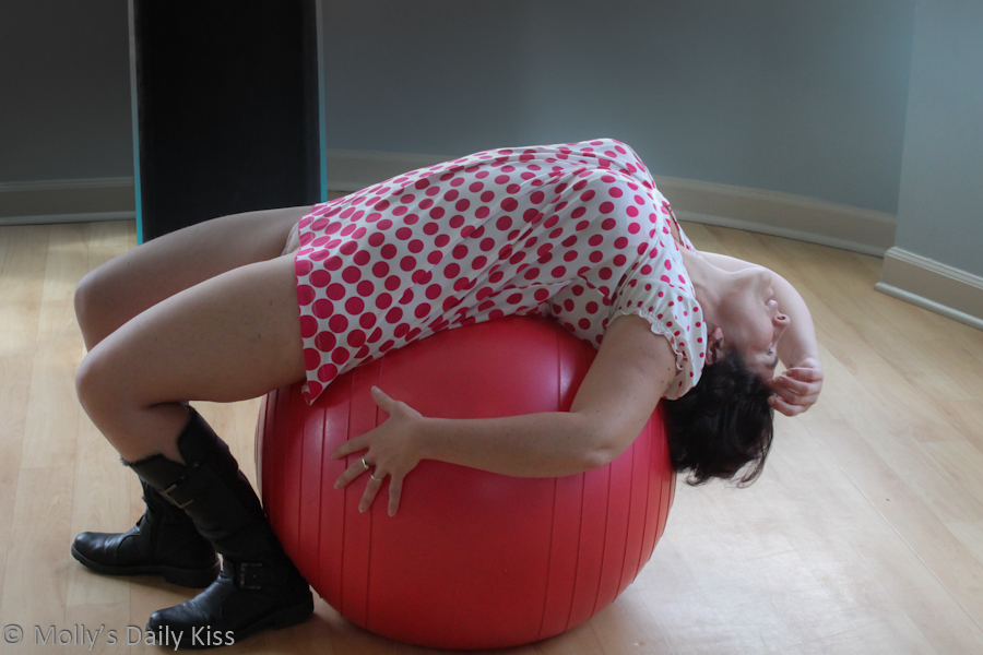 Laying backward over exercise ball