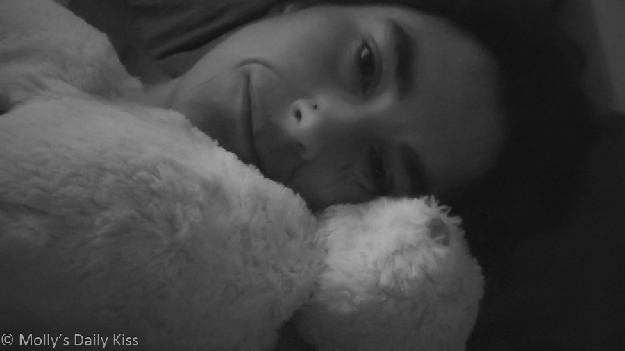 Molly laying in bed with teddy bear