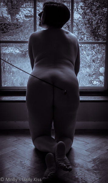 Kneeling with dressage whip on ass