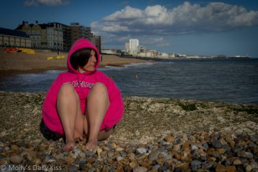 Molly sitting on the beach in Brighton