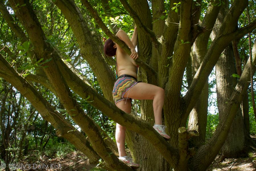 Tom boy climbing tree topless