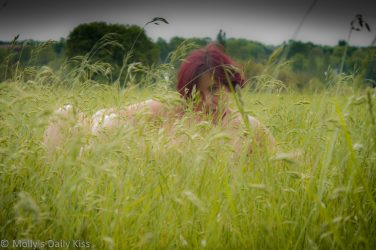 Red head naked in field of long summer grass
