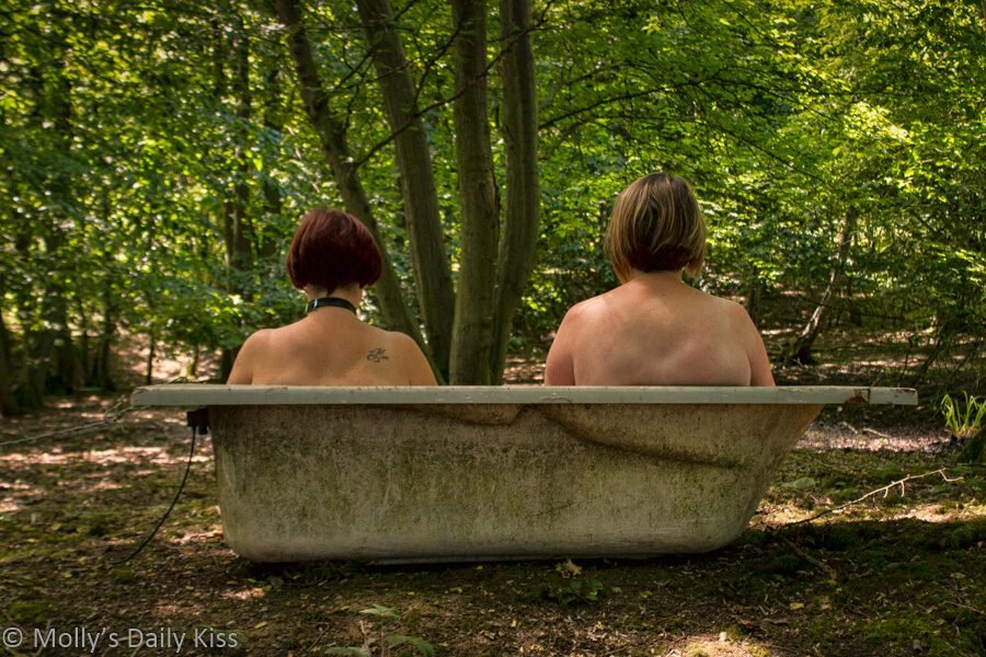 Molly and Exposing 40 sitting in bathtub in woods