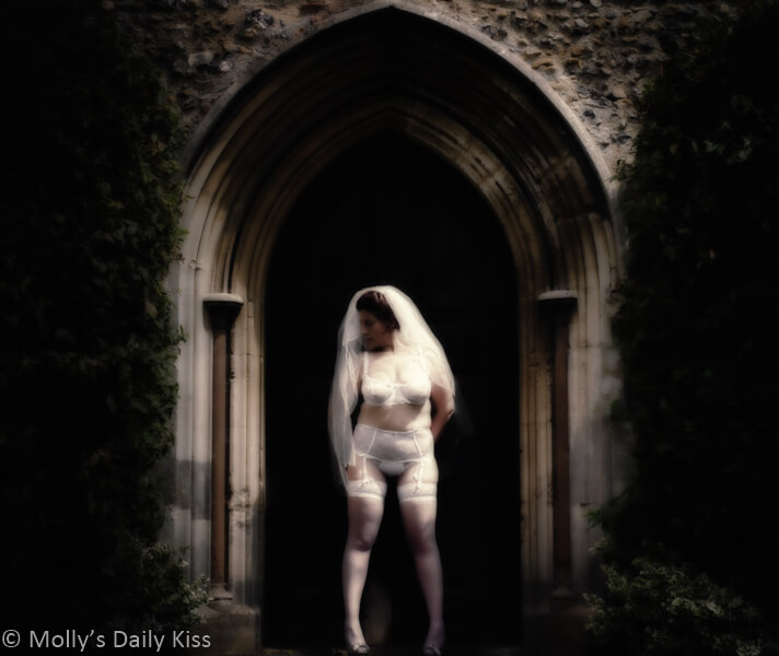 Molly as a bride in lingerie and veil outside church