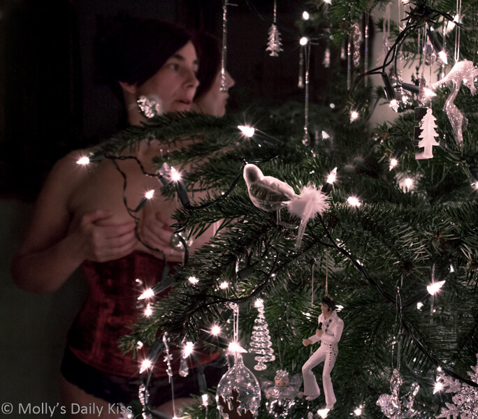 Molly in red corset behind Christmas tree