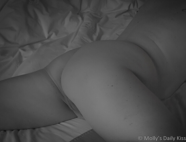 Black and white image of Molly's back and bottom laying on the bed with legs spread