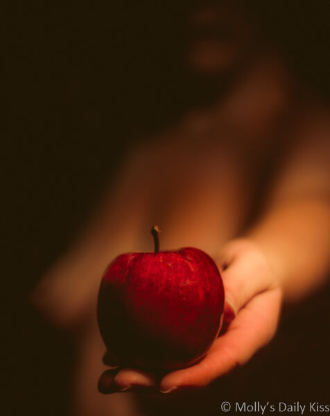 Molly naked holding out bright red apple in her hand