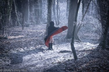 Witch swirling red lined cape in fronty woodland