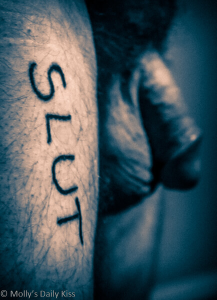 Nude man with the word slut written on his thigh