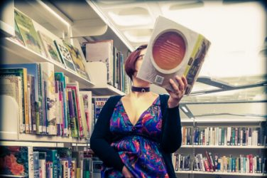 Molly in the library with cooking books and her hand up her skirt