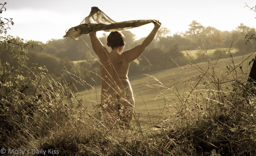 Molly nude standing in field with scarf blowing in the wind looking forward