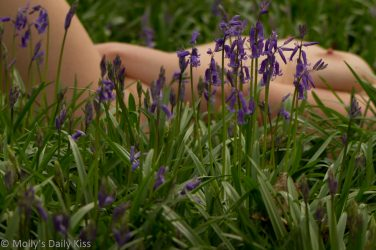 Molly laying nude in the bluebells on the earth