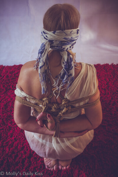 Reconnection. Woman kneeling in submissve position with shibari rope harness