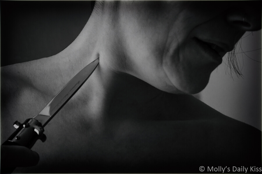 Molly with edge of knife pressed into her neck