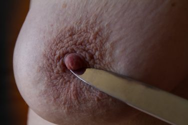 Knife blade point up against nipple