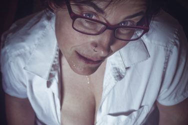 Molly in glasses with cum on her chin and tits out as a footnote