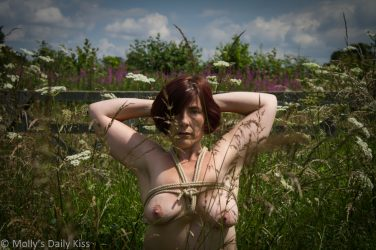 Molly in rope harness in wildflowers meadow field being tenebrous