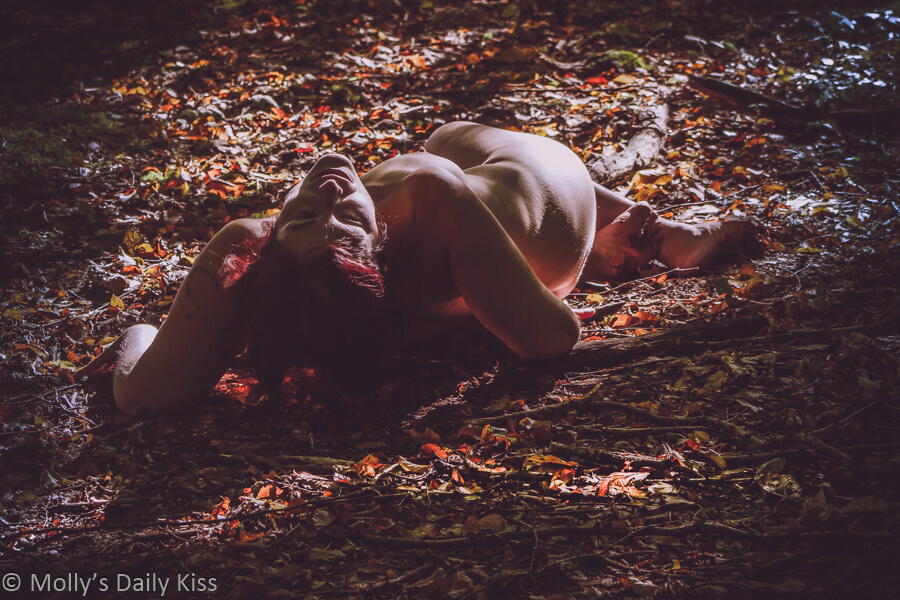 Molly laying on autumn woodland floor nude