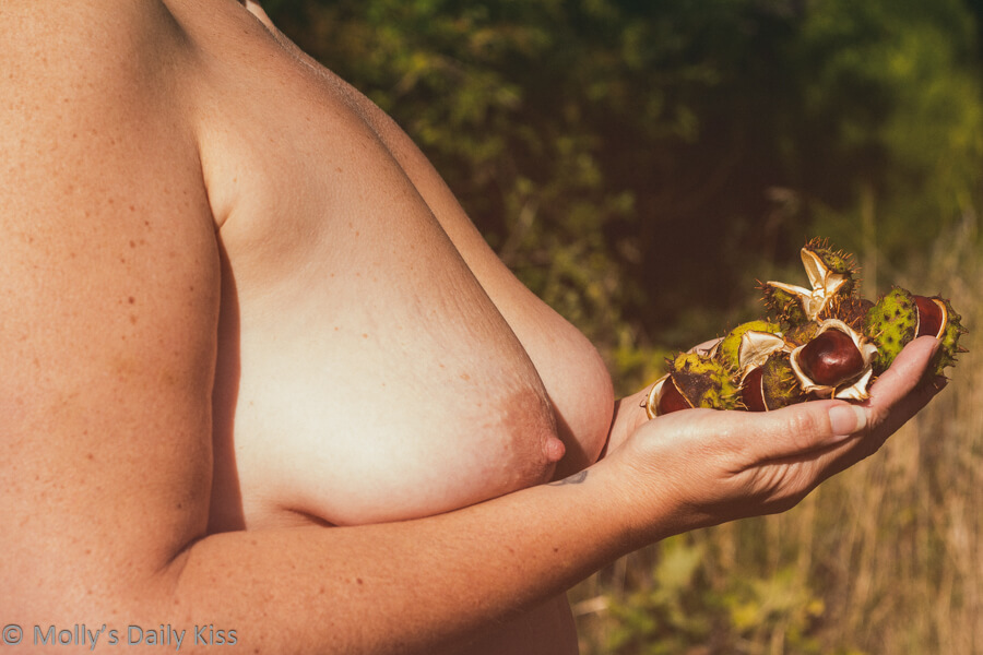 Molly topless is Autumn sunlight holding conkers in calm repose