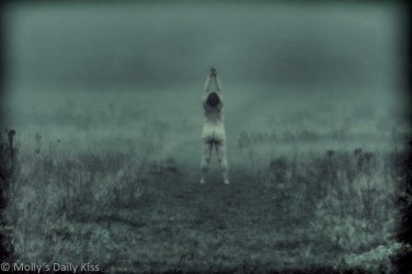 Molly standing naked in the mist reaching up to the sky