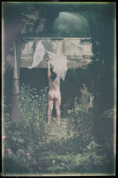 Nude woman reaching up into catching white ghostly figures