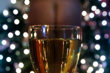 Glass of wine with Molly's bottom inside the glass. New Year Cheer