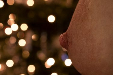 Christmas sparkle lights with boob in the foreground