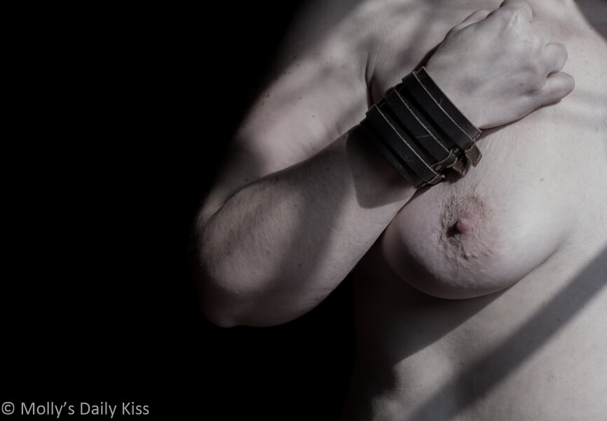 Molly with cuffed wrist across her chest and bare breast