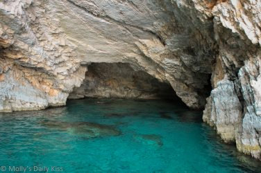 Blue water in cave in Greece. Leading Lady boat